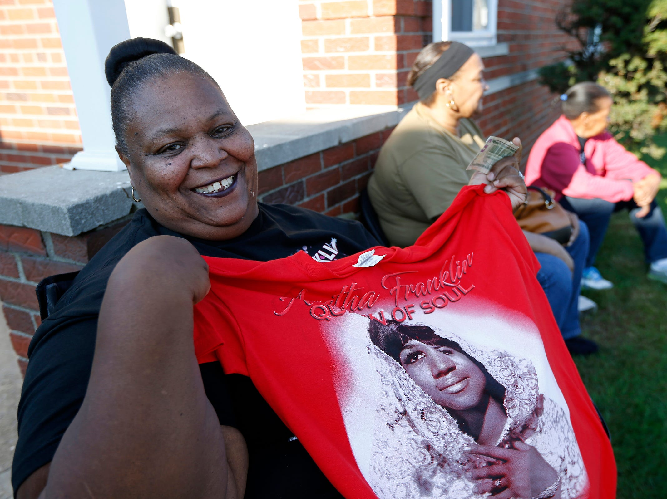 Mary Williams shows off a commemorative t-shirt she purchased during the funeral of Aretha Franklin outside the Greater Grace Temple in Detroit on Friday, Aug. 31, 2018.