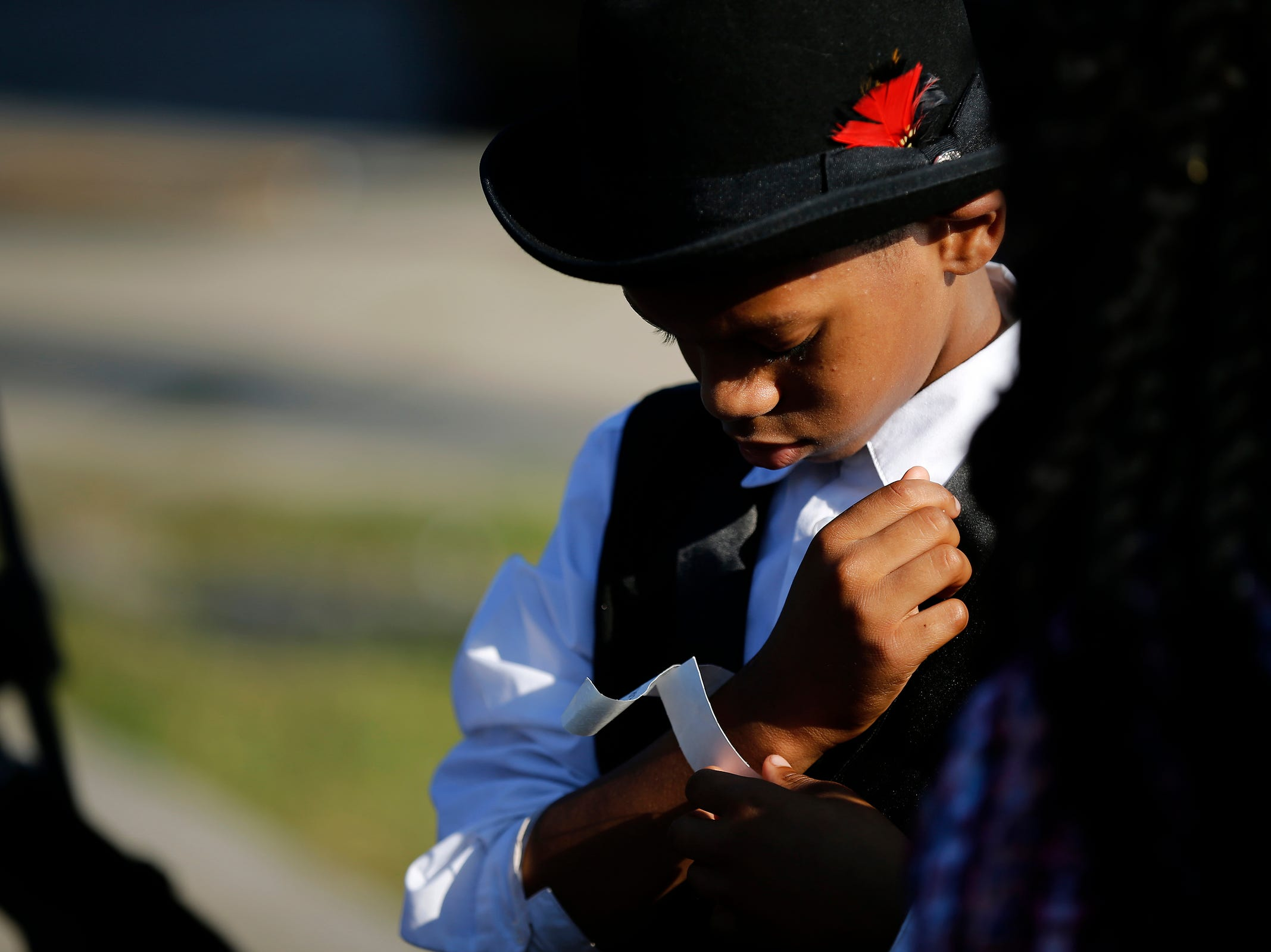 Matthew Smith, 10, wraps a wrist band around his arm before entering the Greater Grace Temple for the funeral of Aretha Franklin in Detroit on Friday, Aug. 31, 2018.