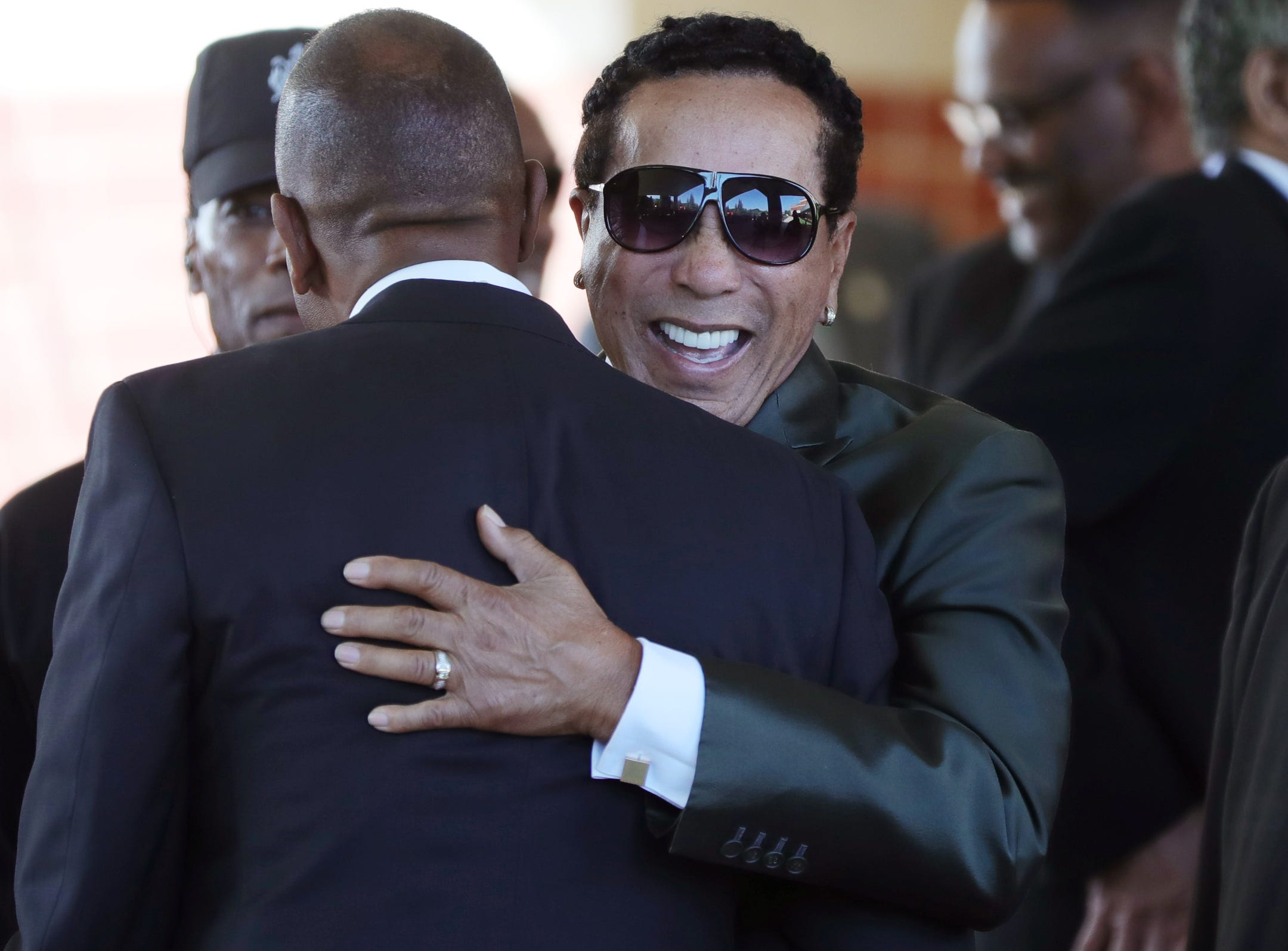 Smokey Robinson smiles as he hugs a man at the entrance of Greater Grace Temple for Aretha Franklin's funeral in Detroit on Friday, August 31, 2018.
