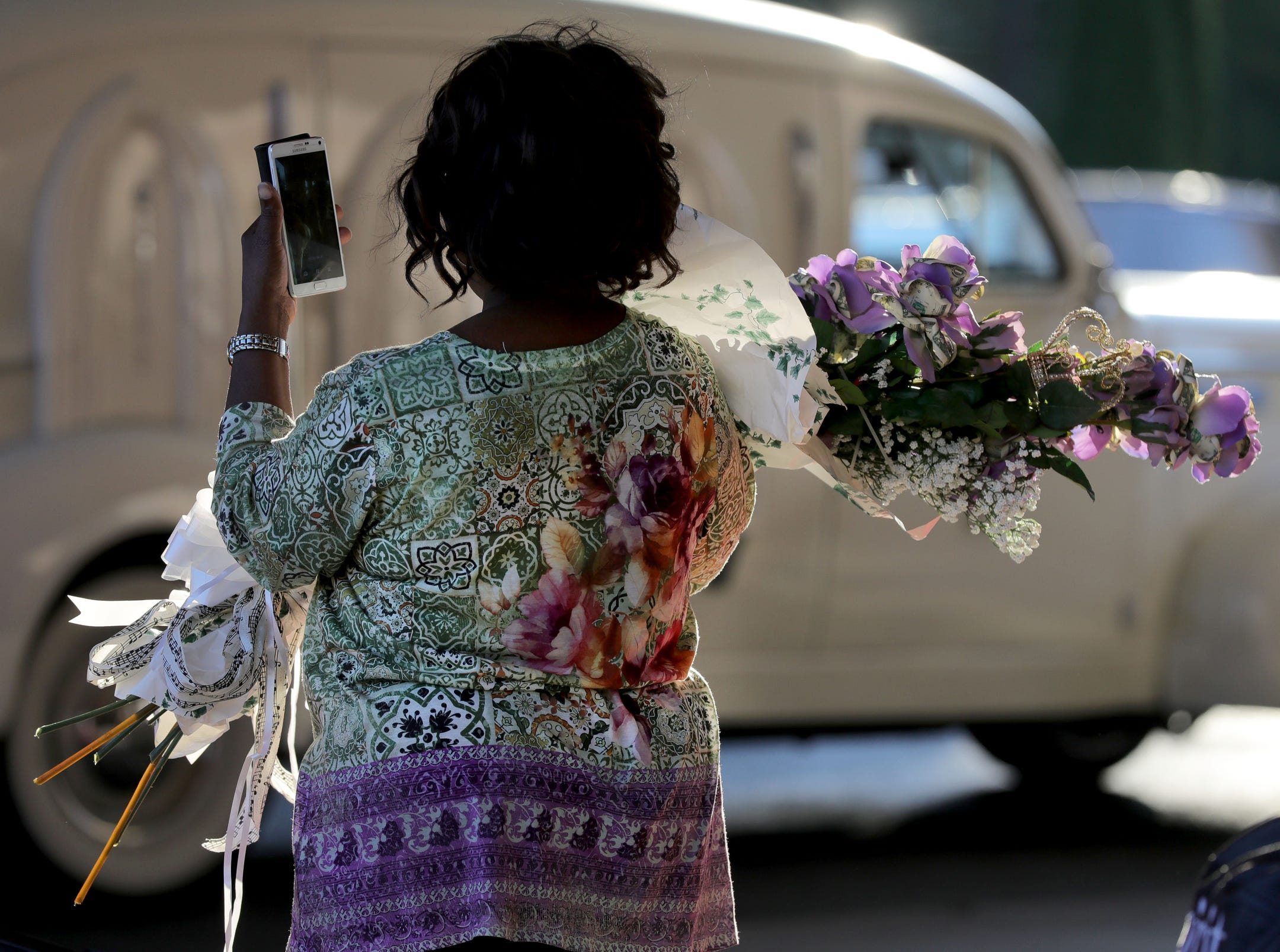 A women takes a picture of the hearse as people arrive at Greater Grace Temple in Detroit to say their final goodbye to Aretha Franklin, Friday, August 31, 2018.  Kirthmond F. Dozier, Detroit Free Press