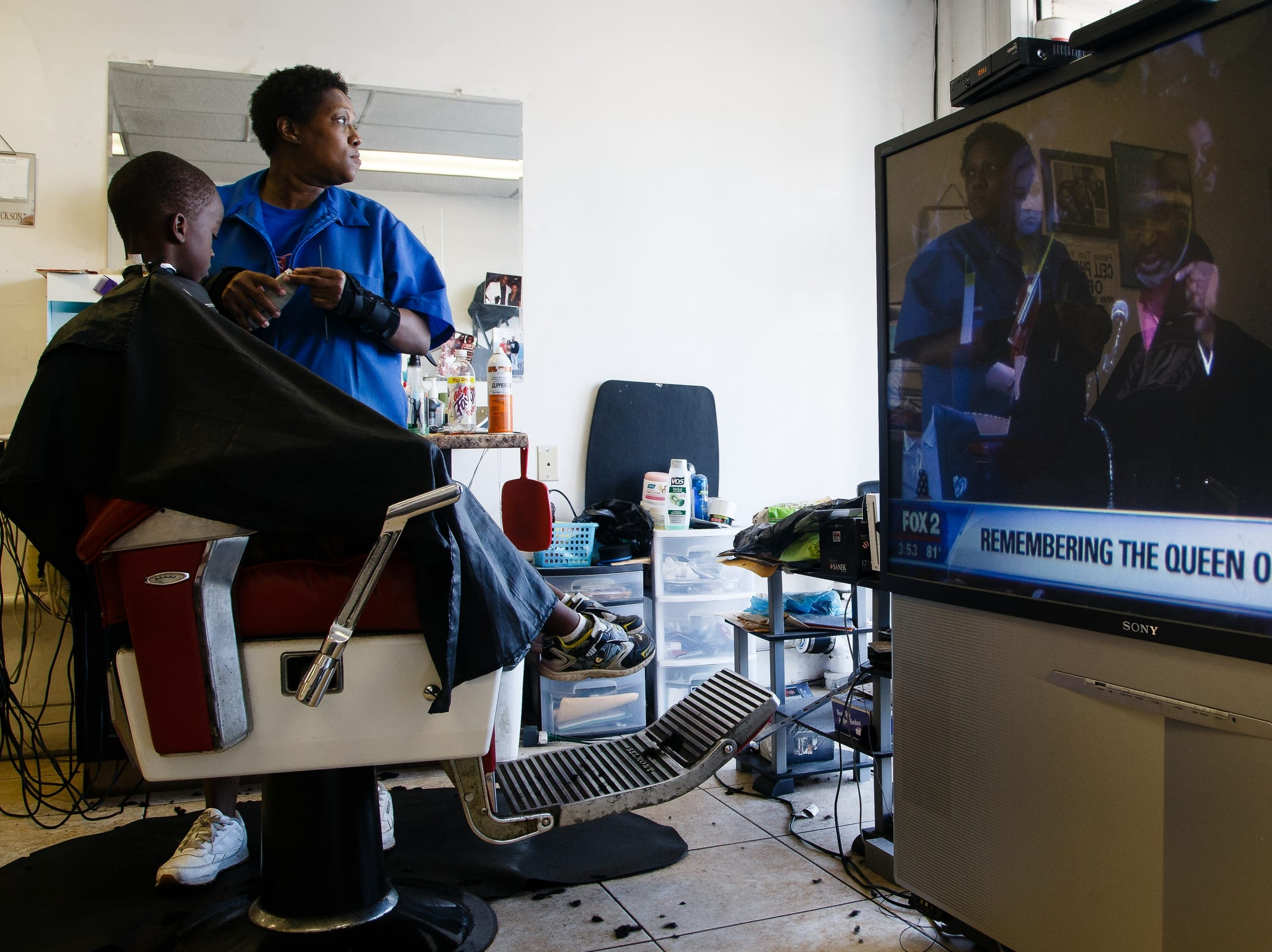 C-Spot Barbershop owner Crystal Jackson, center, cuts hair with Aretha Franklin's funeral on the TV in the background on Friday, Aug. 31, 2018 in Detroit. Franklin died on August 16, 2018.