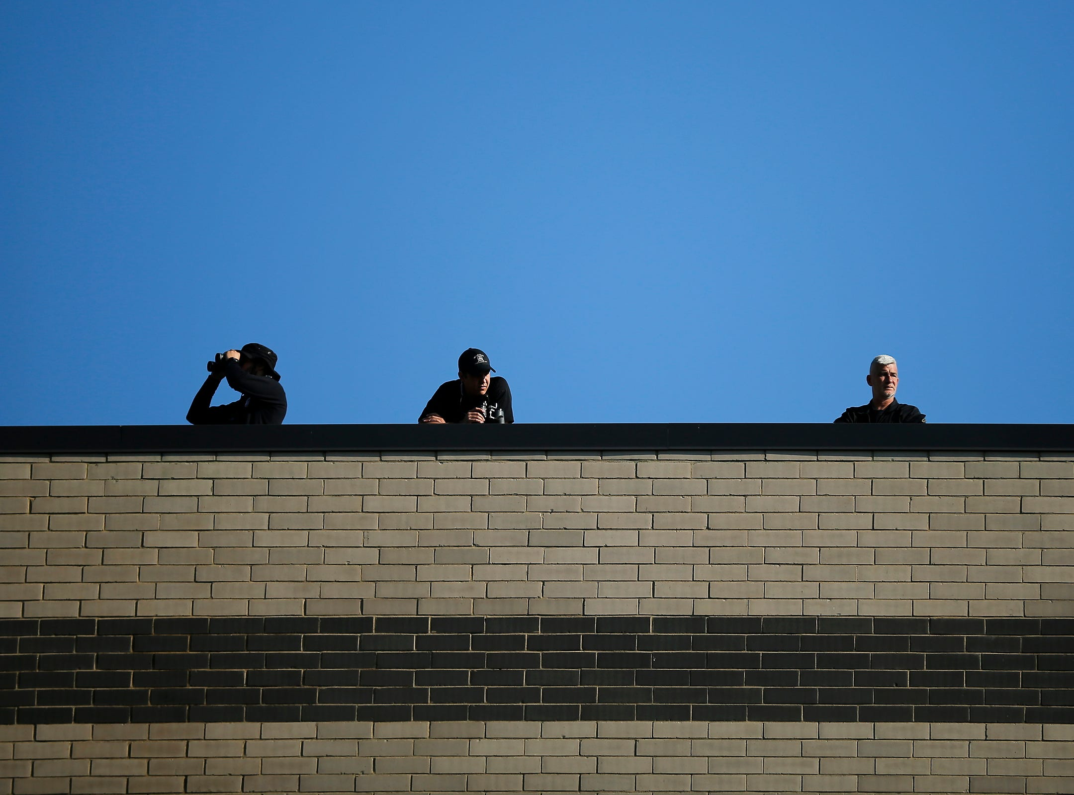 Law enforcement officers watch the crows from the roof of the Greater Grace Temple during the funeral of Aretha Franklin in Detroit on Friday, Aug. 31, 2018.