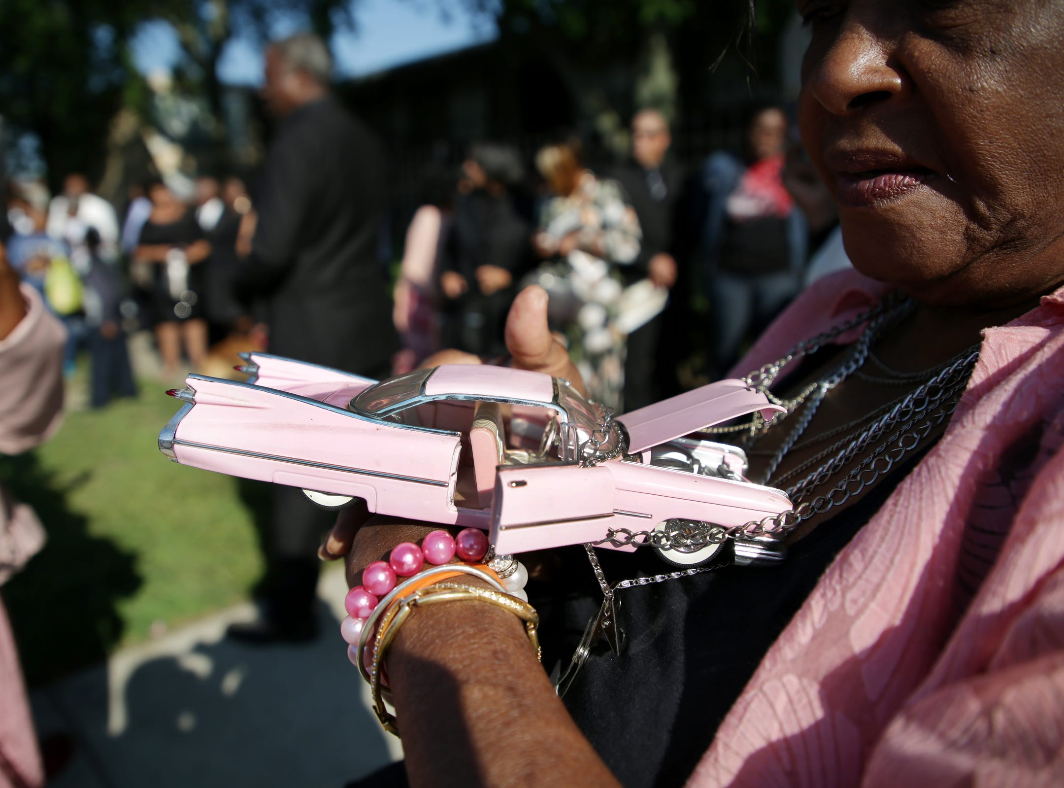 Leola Johnson of Detroit wears a 1959 pink Cadillac necklace as she waits in line for a chance to attend the funeral of Aretha Franklin at Greater Grace Temple on Friday, August 31, 2018.