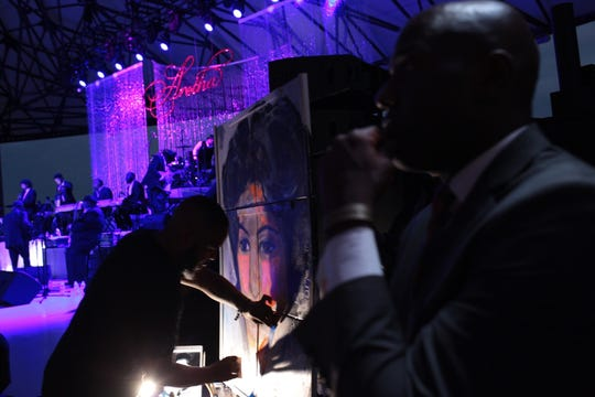Demont Pinder works on a portrait during an Aretha Franklin tribute concert at the Chene Park Amphitheater in Detroit on Thursday, August 30, 2018.