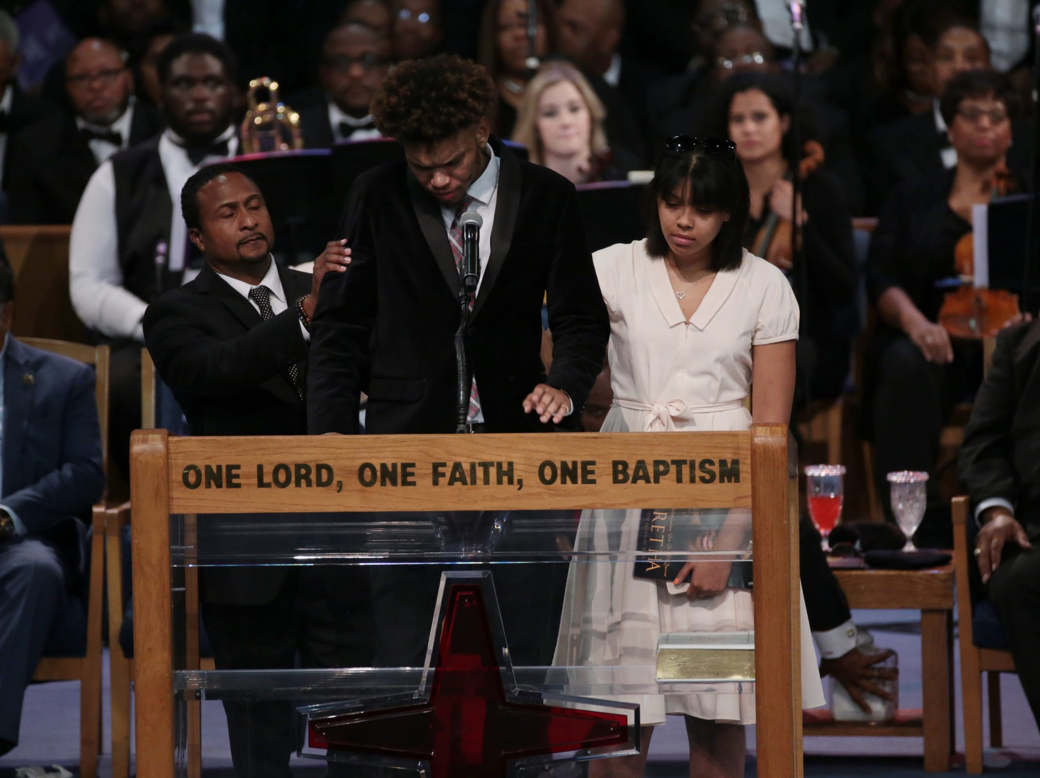 (From left) Aretha Franklin's nephew Vaughn Franklin and her granddaughter Victorie Franklin comfort her grandson Jordan Franklin as he speaks during the funeral for the late Aretha Franklin at Greater Grace Temple in Detroit on Friday, August 31, 2018.