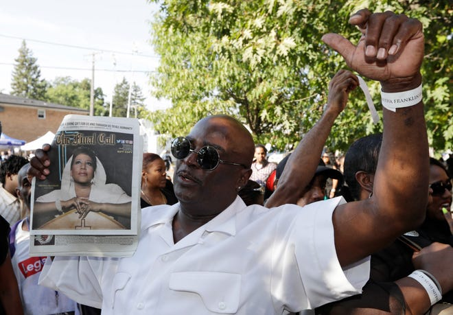 """Roger Chambers holds up an issue of """"The Final Call,"""" featuring a photograph of Aretha Franklin outside Greater Grace Temple Friday morning."""