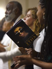 A funeral attendee holds a program during Aretha Franklin's memorial service at Greater Grace Temple in Detroit.