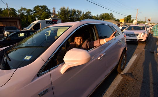 Pink Cadillac drivers wave during the procession.
