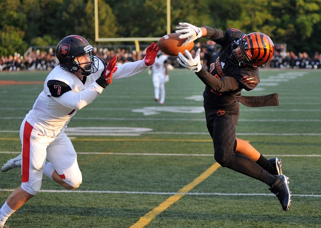 Belleville wide receiver Darrell Johnson (13), right, reaches but cannot haul in the pass as Livonia Churchill defender Avery Grenier (7) defends him in the first quarter.