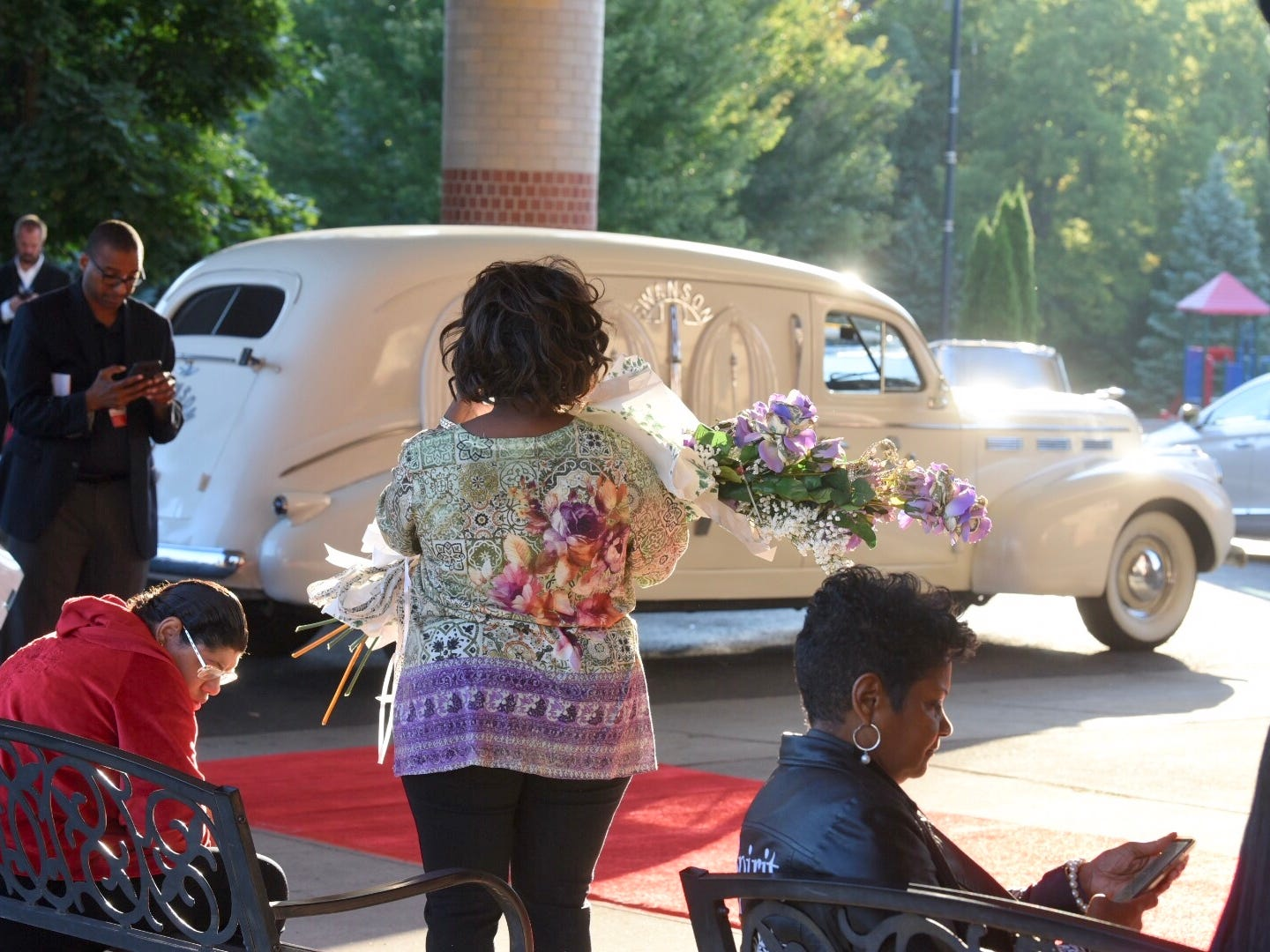 A woman holds flowers in tribute to Aretha Franklin outside Greater Grace Temple.