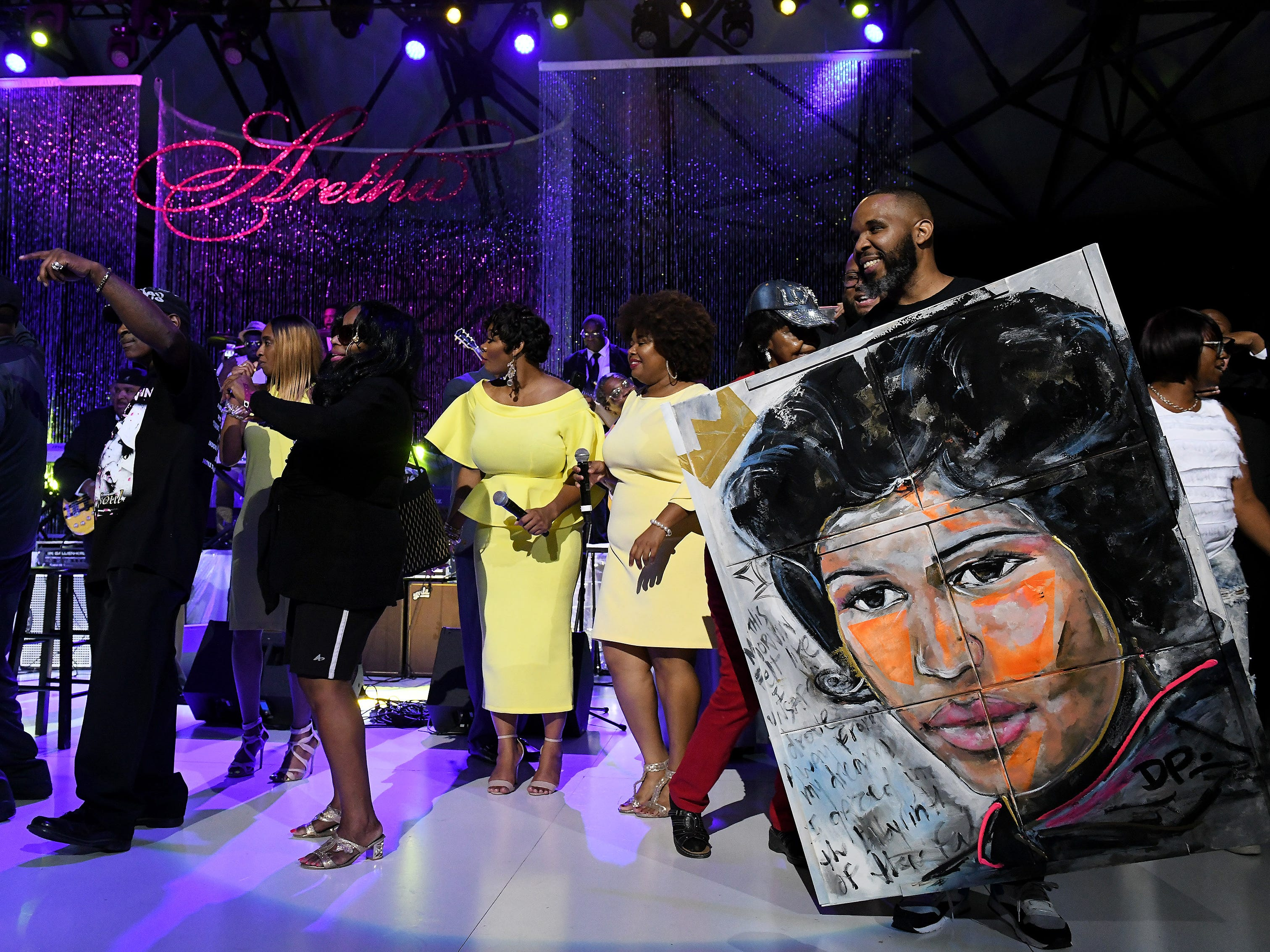 Artist Demont Pinder, right, from New York holds the painting he created during the concert.