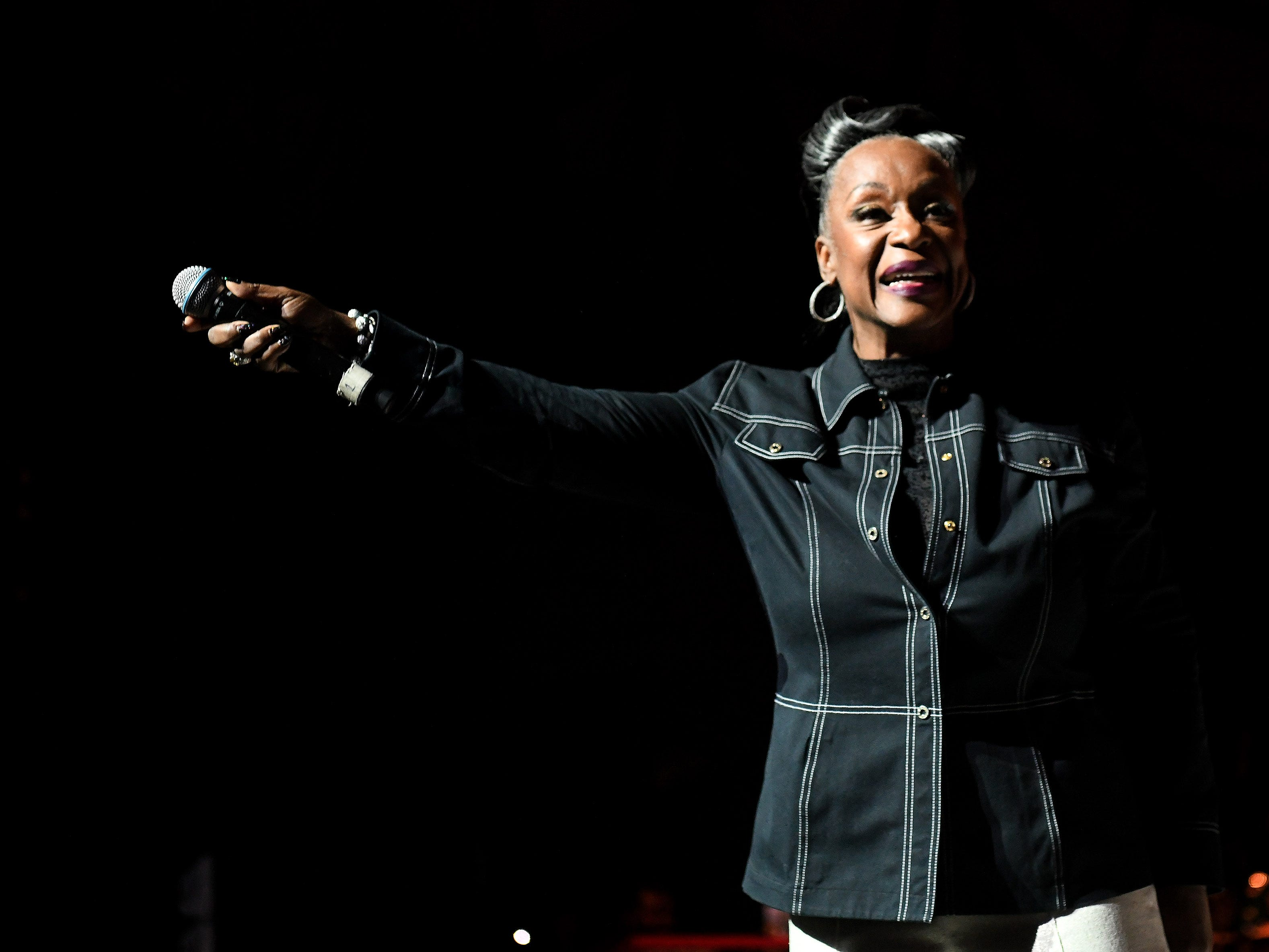 "Regina Belle holds the microphone towards the audience while performing ""Rock Steady."""