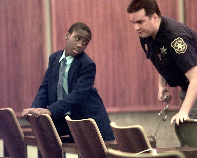 Nathaniel Abraham, 13, of Pontiac, Michigan has his leg-shackles removed by an Oakland County Sheriff Deputy in the Oakland County Board of Commissioners Auditorium prior to the start of jury selection at his murder trial on Oct. 18, 1999.
