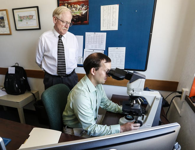 Fond du Lac County Chief Medical Examiner Dr. Erik Mitchell watches as Medical Examiner Adam Covach looks in a microscope Friday, August 31, 2018, at their office in Fond du Lac, Wisconsin. Doug Raflik/USA TODAY NETWORK-Wisconsin