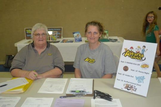 Jane Cruz, left, and Casey Lawrence register children for the Awana program at Fremont Alliance Church's registration and ice cream social night.
