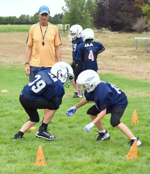 Coach Mark Keyworth oversees a tackling drill while teaching players on his fifth- and sixth-grade Cowboys team in the city of Fort Collins youth football program proper tackling technique during a practice Thursday at a neighborhood park in Windsor.