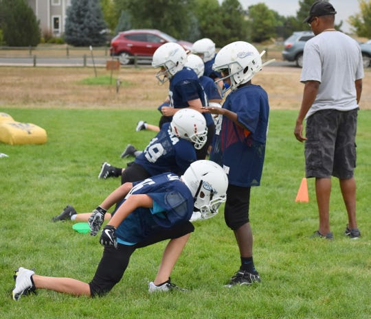 Players go through form-tackling drills in slow motion Thursday during a practice in Windsor of the fifth- and sixth-grade Cowboys football team the city of Fort Collins youth football program.
