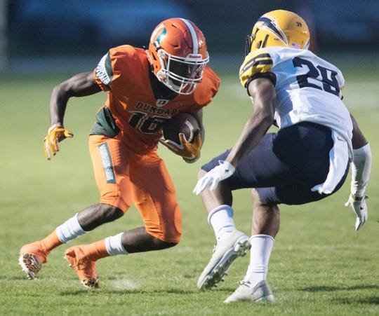 Dunbar High School's Tionte Hatcher eludes Lehigh's Ahmere Dixon on Thursday at Dunbar in Fort Myers. Lehigh beat Dunbar 12-6.