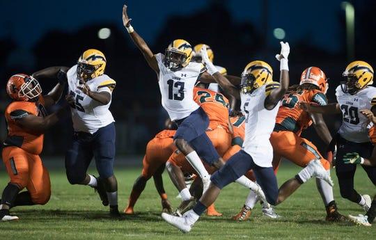 Lehigh High School's Omarion Cooper (13), center, blocks a Dunbar extra point on Thursday at Dunbar in Fort Myers. Lehigh beat Dunbar 12-6.