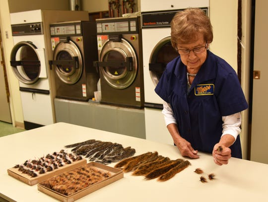 Peg Doucette inspects the tails from fox squirrels and gray squirrels, which provide hair tied to treble hooks on Mepps fishing lures.