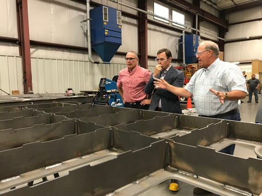 Kevin Gosselin, left, and John West, right, of Fox Valley Metal-Tech explain part of a watertight door to U.S. Rep. Mike Gallagher during a tour on Aug. 27. The door will be part of a U.S. Navy littoral combat ship.