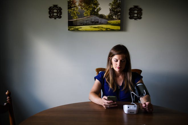 Jenny Williams uses a smartphone application to check her blood pressure to send to her doctor inside her home on Friday, Aug. 31, 2018. The app helps women cut down on the number of trips to the doctor while pregnant.