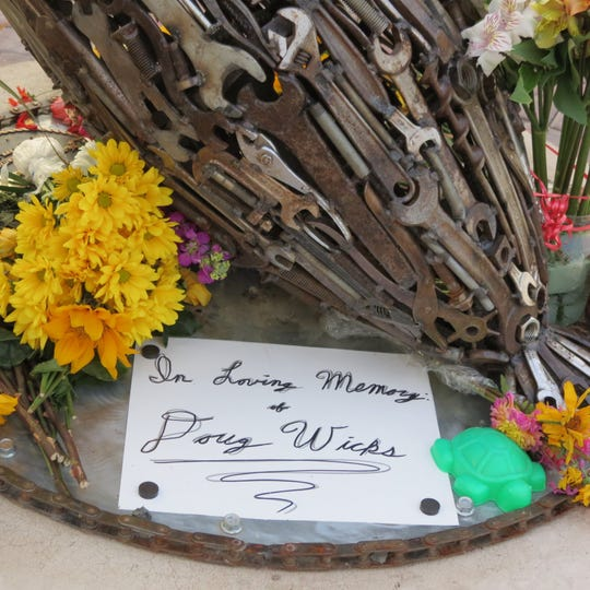 """""""In loving memory of Doug Wicks"""" reads a sign at a pelican dedicated to him along the River's Edge Trail."""
