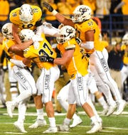 Montana State safety Brayden Konkol jumps on defensive end Bryce Sterk in celebration after Sterk's sack in the last quarter of their NCAA college football game at Bobcat Stadium, Thursday, Aug. 30, 2018, in Bozeman, Mont.