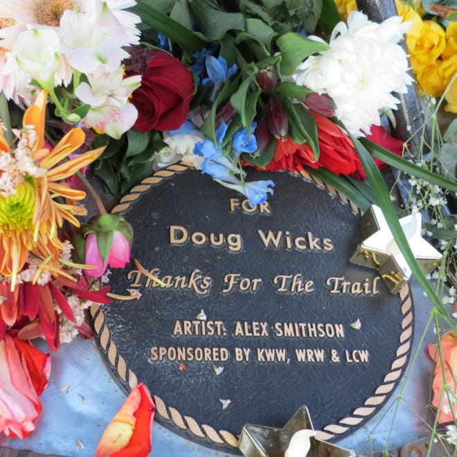 """A plaque on a pelican sculpture along the River's Edge Trail reads: """"For Doug Wicks. Thanks for the trail."""" It's surrounded by flowers left in homage to Wicks, who died after more than two decades building the trail."""