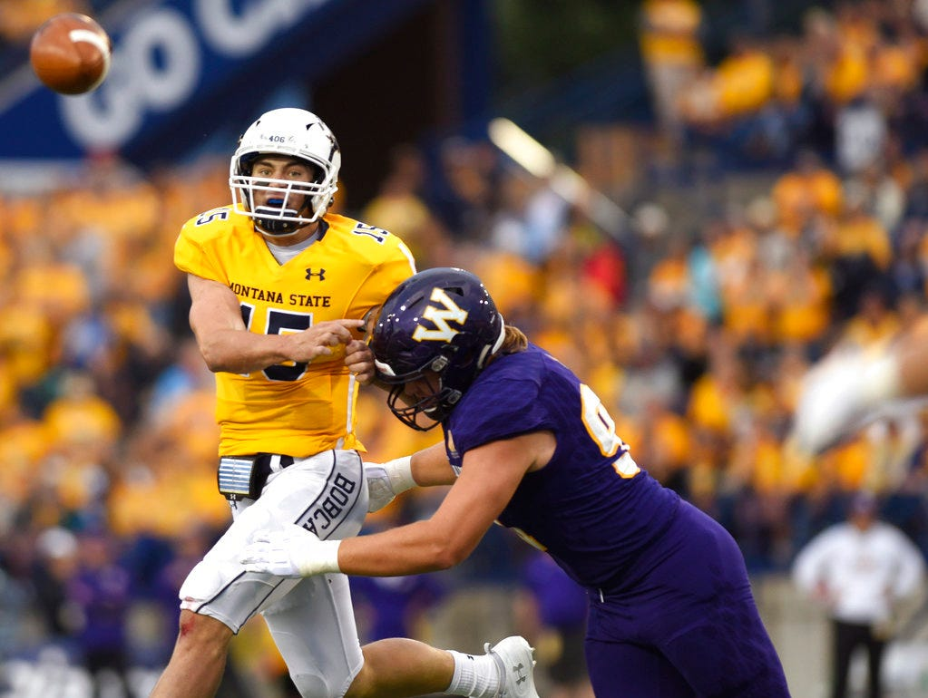 Montana State quarterback Troy Anderson, left, squeezes off a pass before being taken out by Western Illinois' Kyle Williams during an NCAA college football game at Bobcat Stadium, Thursday, Aug. 30, 2018, in Bozeman, Mont.