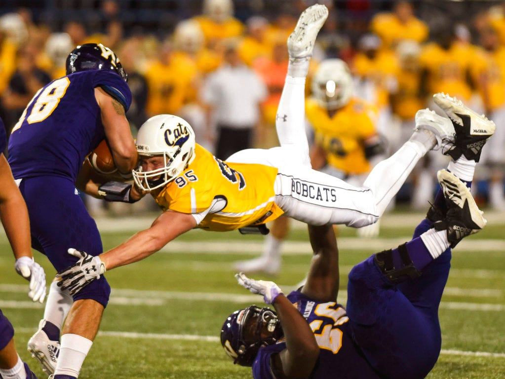 Montana State defensive lineman Derek Marks jumps over Western Illinois' Michael Ross to take down Western Illinois' quarterback Sean McGuire during an NCAA college football game at Bobcat Stadium on Thursday, Aug. 30, 2018, in Bozeman, Mont.
