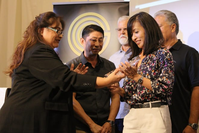 Vuong Duong /For Pacific Daily NewsArchway, Inc.  Vice President Mika Caldwell, right, and President Richard Chan, center, receive the Small Business Excellence Award during the Small Business Expo and Outreach.