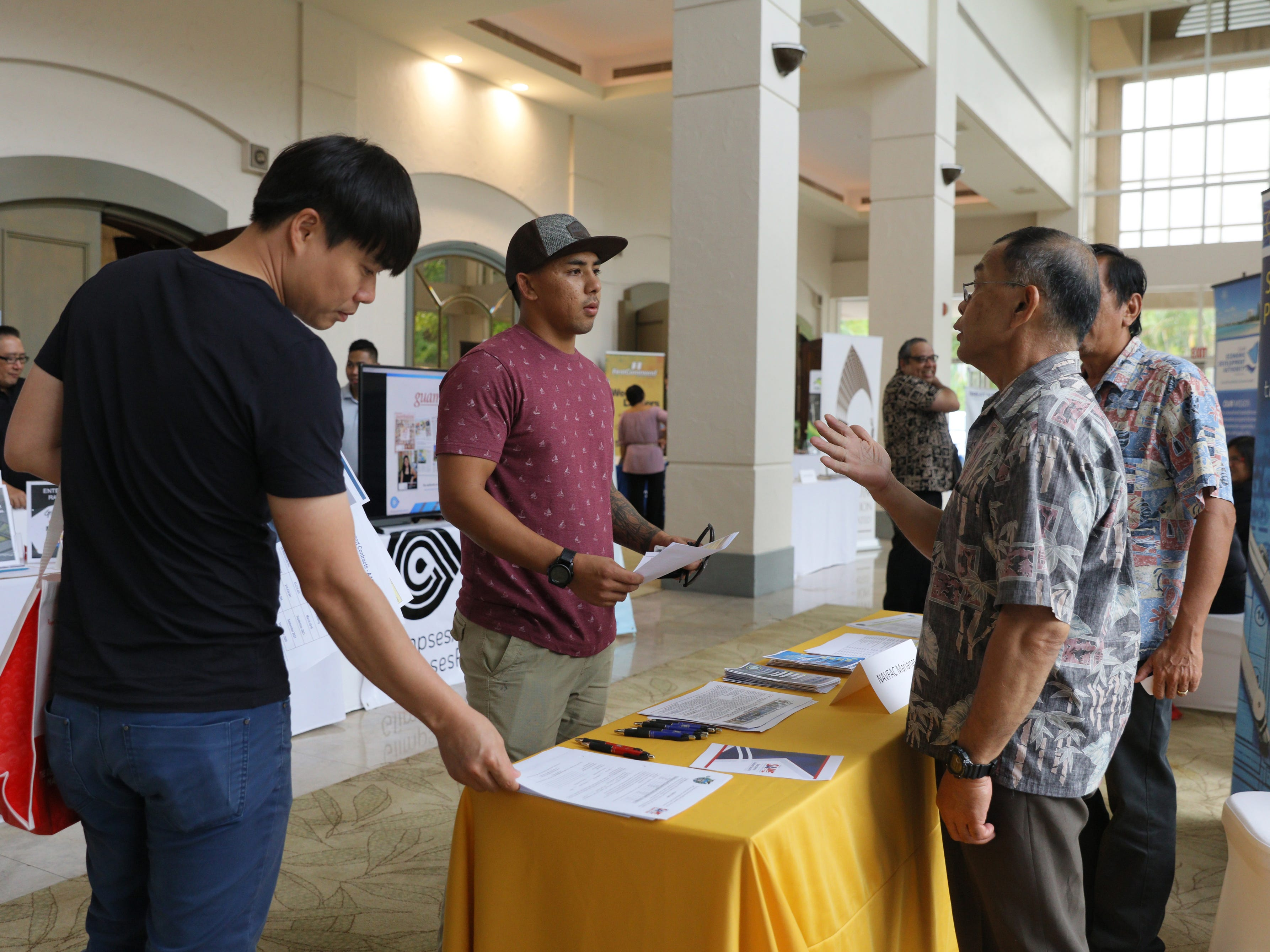 Victor Taitano, second from left, inquires about registration with NAVFAC  representatives during the Small Business Expo and Outreach.