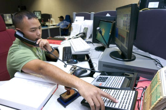 In this October 2010 file photo, emergency medical dispatcher Peter J. San Nicolas takes a call at the 911 police/fire emergency dispatch center in Agana Heights. Guam's  911 system is two decades old, and the administration has spent $ 4 million in 911 system funds on other government expenses.