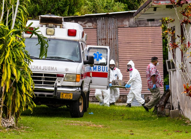 Guam Fire Department firefighters carry a body to an awaiting ambulance as Guam Police Department personnel conduct a death investigation at a home along Macheche Road in Dededo on Friday, Aug. 31, 2018.