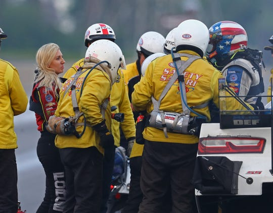 John Force (right) was helped from his car by the safety team after crashing into the wa on June 2l. Daughter Courtney Force looked on at left.