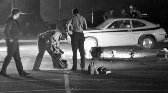 Police use a power saw to cut asphalt where a bomb exploded Sept 6, 1978.  A series of bombs exploded in Speedway in 1978 terrorizing the town.