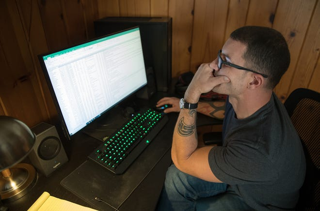 Josh Russell, a systems analyst, at his Indianapolis home, works during his free time as an internet troll hunter, Wednesday, Aug. 29, 2018. Russell is about two weeks out from a series of media interviews, including CNN, and says that he's receiving more attention from trolls, including being doxed, where his home address information was made public.