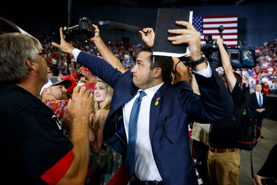 A volunteer member of the advance team for President Donald Trump blocks a camera as a photojournalist attempts to take a photo of a protester during a campaign rally at the Ford Center, Thursday, Aug. 30, 2018, in Evansville, Ind.