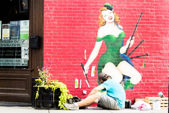 Curtis Glover paints a mural on the outside of Boyd's Jig & Reel on Aug. 29. Glover will be participating in a live art competition during First Friday on Sept. 7.
