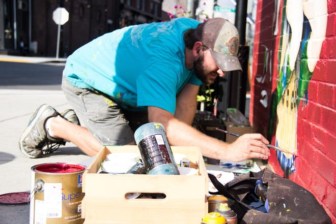 Curtis Glover, known for his detailed murals, paints on the outside of Boyd's Jig & Reel on Aug. 29. On Sept. 7, he will be participating in First Friday, which he said is important for young artists to attend.
