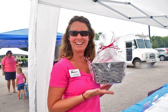 Dr. Jennifer Scoles with Scoles Family Chiropractic organizes the many door prizes donated to the event by Karns businesses during the Back to School Bash held at Beaver Creek Dental Saturday, Aug. 25, 2018.