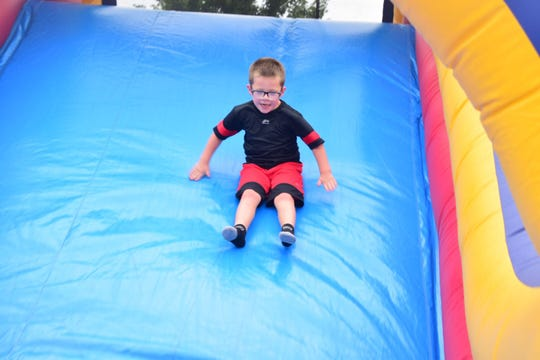 Cameron Douglas, 5, makes his way down an inflatable slide at the Back to School Bash held at Beaver Creek Dental Saturday, Aug. 25, 2018.