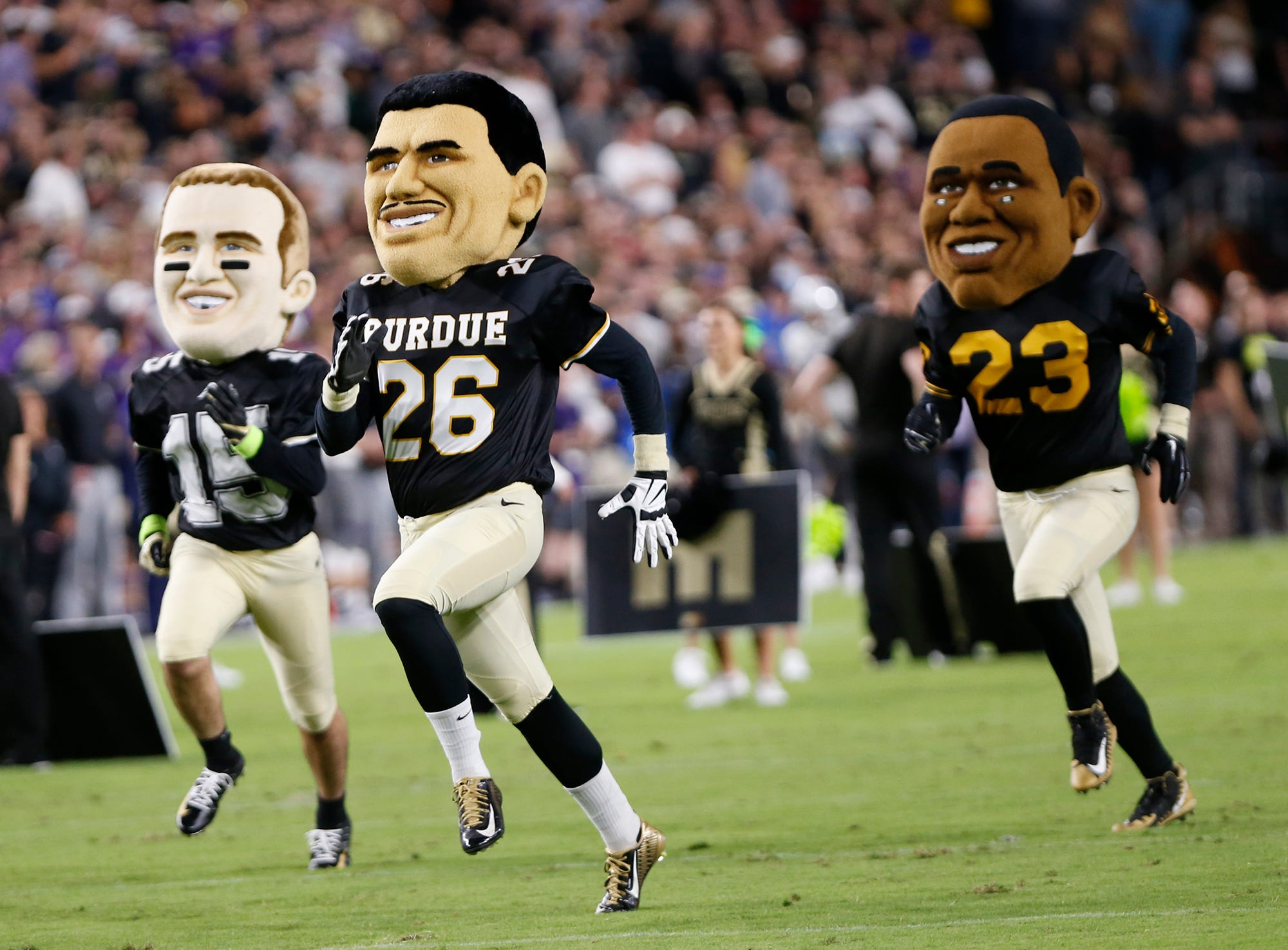 Big heads of former Purdue greats Drew Brees, from left, Rod Woodson and Leroy Keyes sprint the lenght of the field during a timeout of the Boilermakers game with Northwestern Thursday, August 30, 2018, in West Lafayette. Northwestern defeated Purdue 31-27.