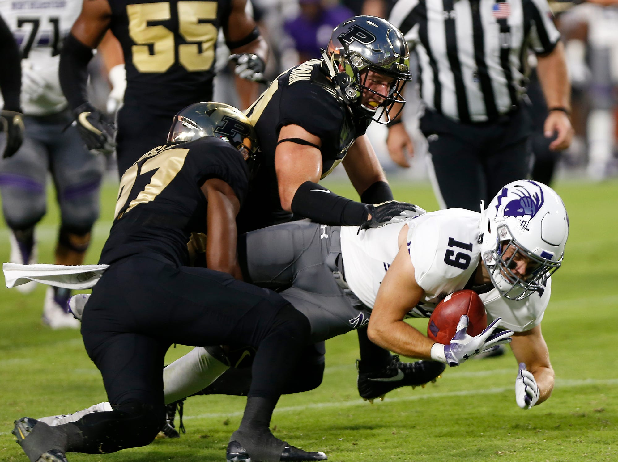 Riley Lees of Northwestern lunges for additional yardage on a carry against Purdue Thursday, August 30, 2018, in West Lafayette.