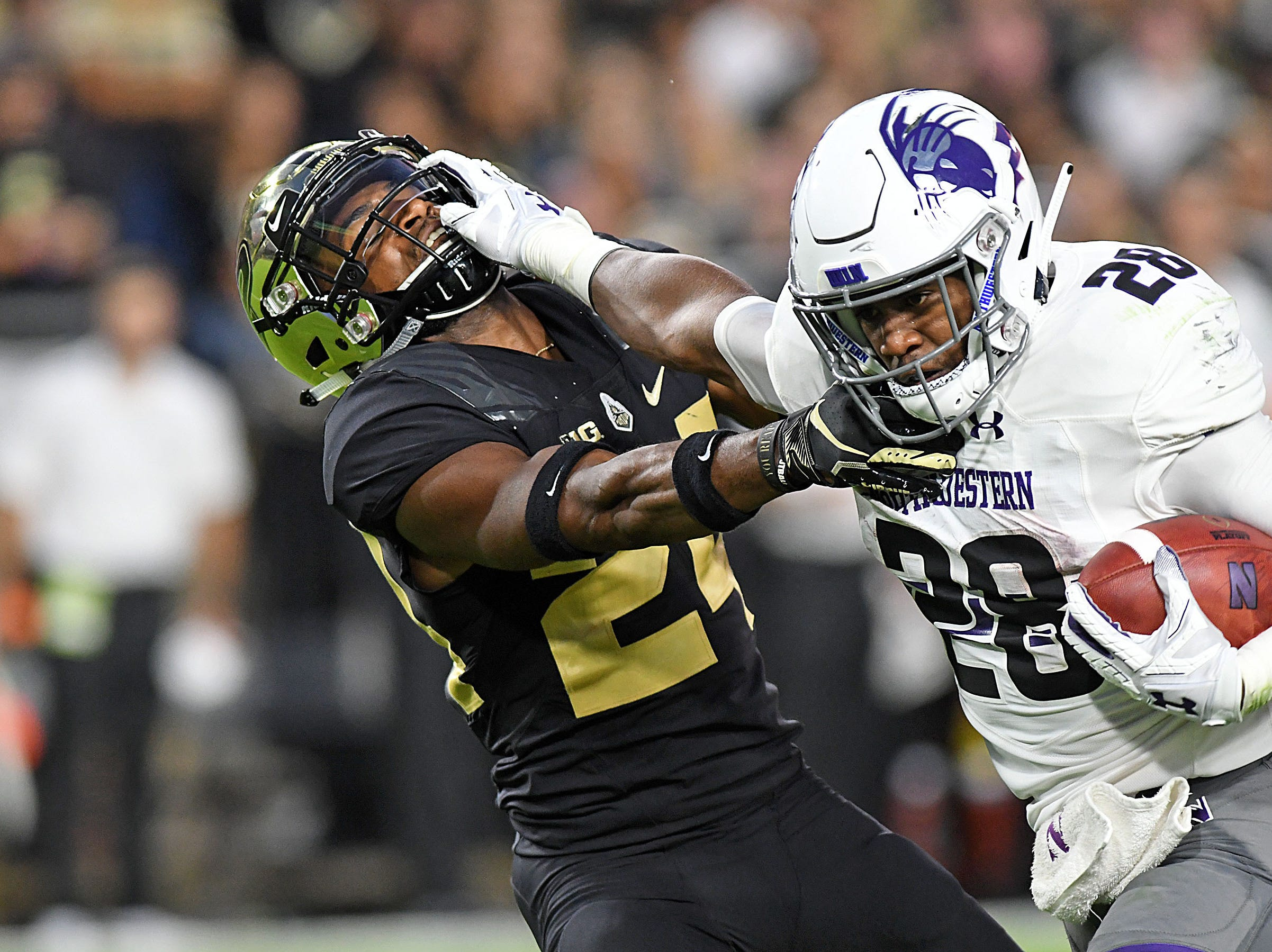 Aug 30, 2018; West Lafayette, IN, USA; Northwestern Wildcats running back Jeremy Larkin (28) stiff arms  Purdue Boilermaker corner back Tim Carson (24)   in the first half  at Ross-Ade Stadium. Mandatory Credit: Thomas J. Russo-USA TODAY Sports