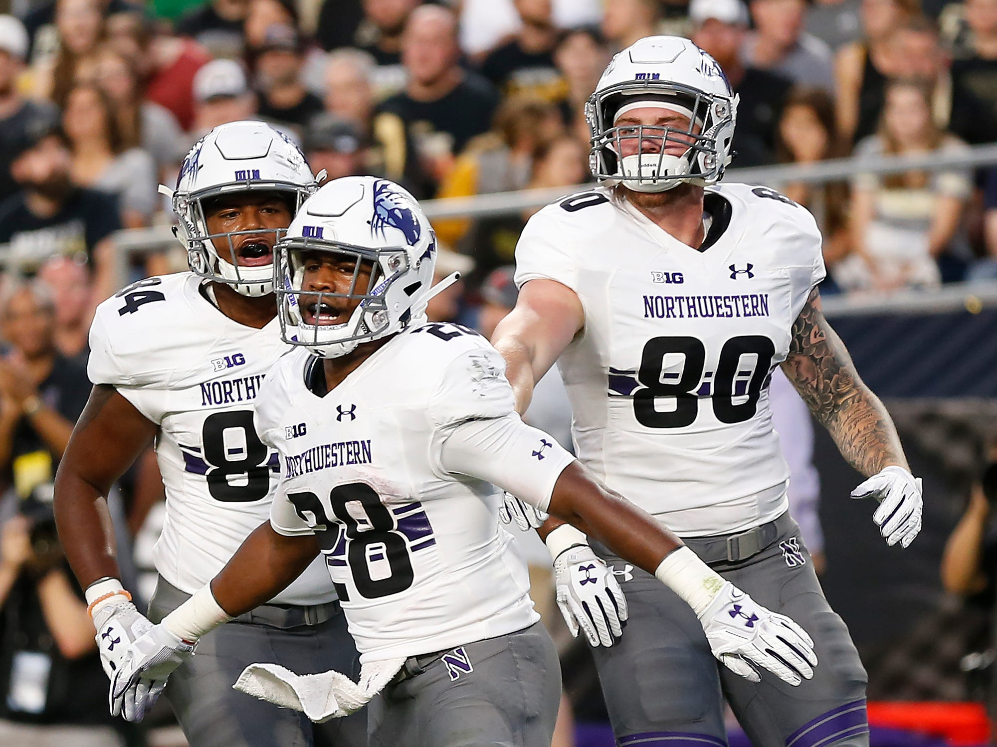 Jeremy Larkin of Northwestern (28) celebrates with teammates Cameron Green (84) and Trey Pugh (80) after his rushing touchdown at 7:58 in the first quarter against Purdue Thursday, August 30, 2018, in West Lafayette.