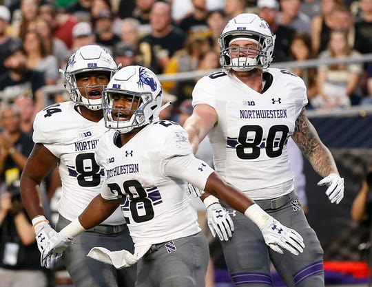 Jeremy Larkin of Northwestern (28) celebrates with teammates Cameron Green  (84) and d4ad3f072