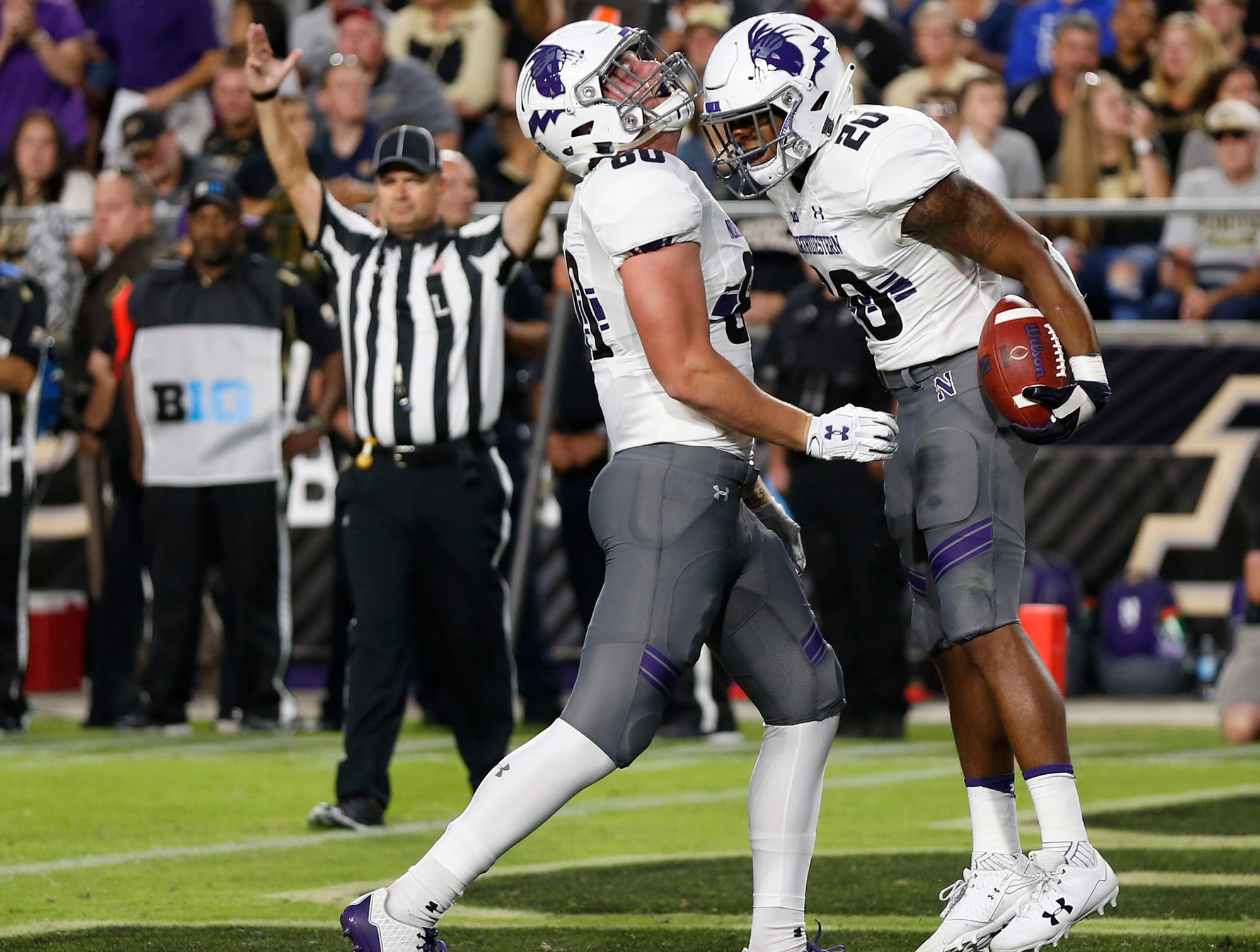 Jeremy Larkin of Northwestern celebrates with teammate Trey Pugh after his rushing touchdown against Purdue at 5:34 in the first quarter Thursday, August 30, 2018, in West Lafayette. Northwestern lead 14-0 after Larkin's score.