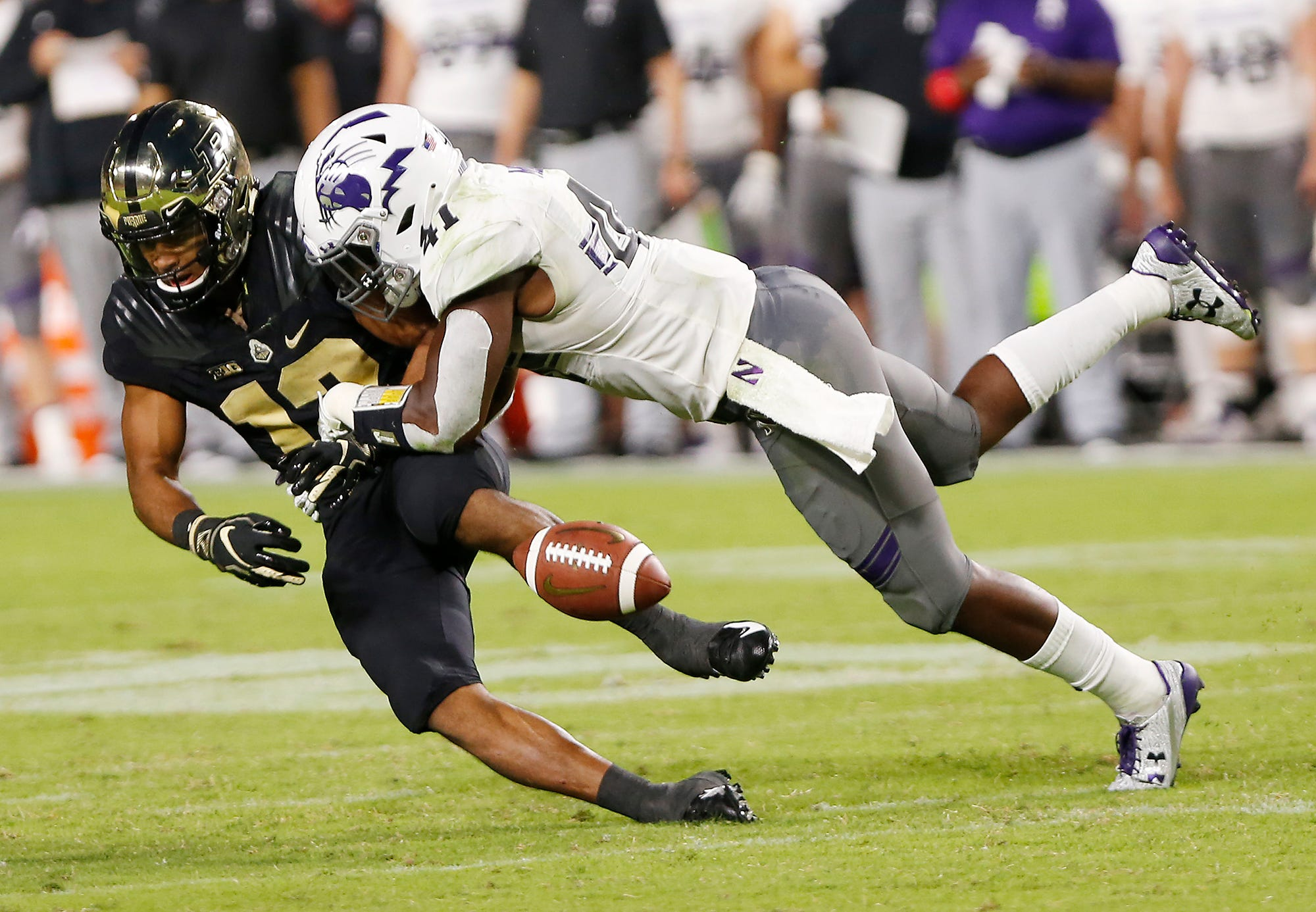 Jared Sparks of Purdue can't come up with a catch as he is hit by Jared McGee of Northwestern in the second quarter Thursday, August 30, 2018, in West Lafayette.